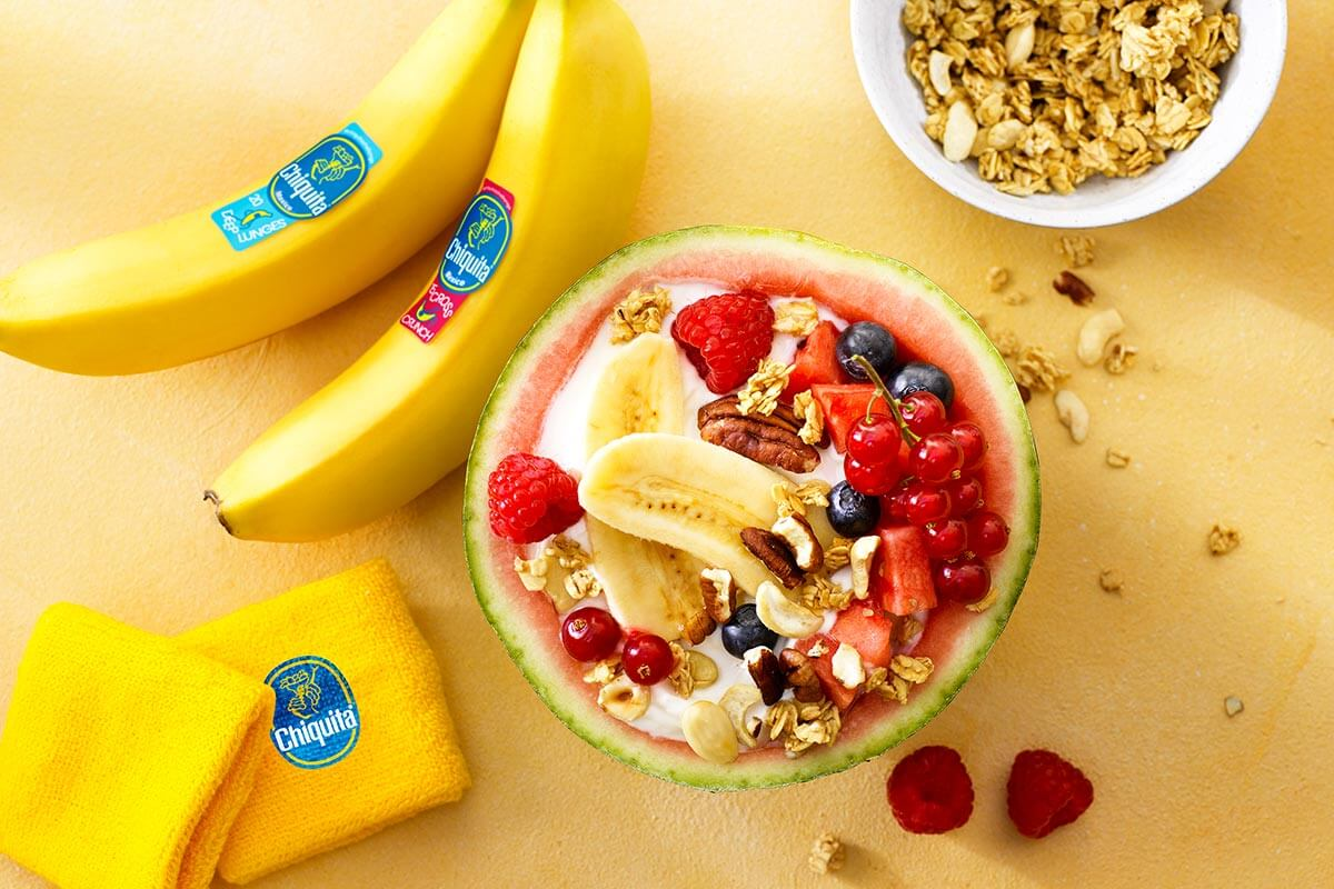 Fruit salad in a watermelon, stuffed with organic yogurt, Chiquita bananas, red fruit, seeds and nuts